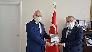 Dr. Çamlı, Kula'nın yeni kitabını kurum amirlerine hediye etti